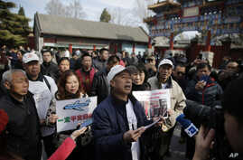 Relatives of passengers on board the missing Malaysia Airlines Flight 370 speak to journalists during a gathering outside the Yonghegong Lama Temple in Beijing on the two year anniversary, Tuesday, March 8, 2016.
