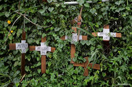 FILE - Cardboard crosses with the names of opposition supporters killed during demonstrations are seen on a fence during a strike called to protest against Venezuelan President Nicolas Maduro's government in Caracas, Venezuela, July 20, 2017.