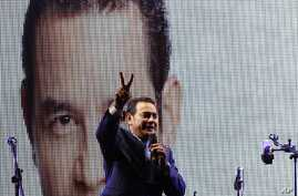 Television comedian and presidential candidate for the National Front of Convergence party Jimmy Morales, flashes a victory sign to his supporters at his party headquarters in Guatemala City, Sunday, Sept. 6, 2015.