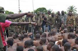 Soldiers loyal to Alassane Ouattara point to men they claim to recognize among several dozen prisoners captured during fighting and patrols in Abidjan, Ivory Coast, April 6, 2011