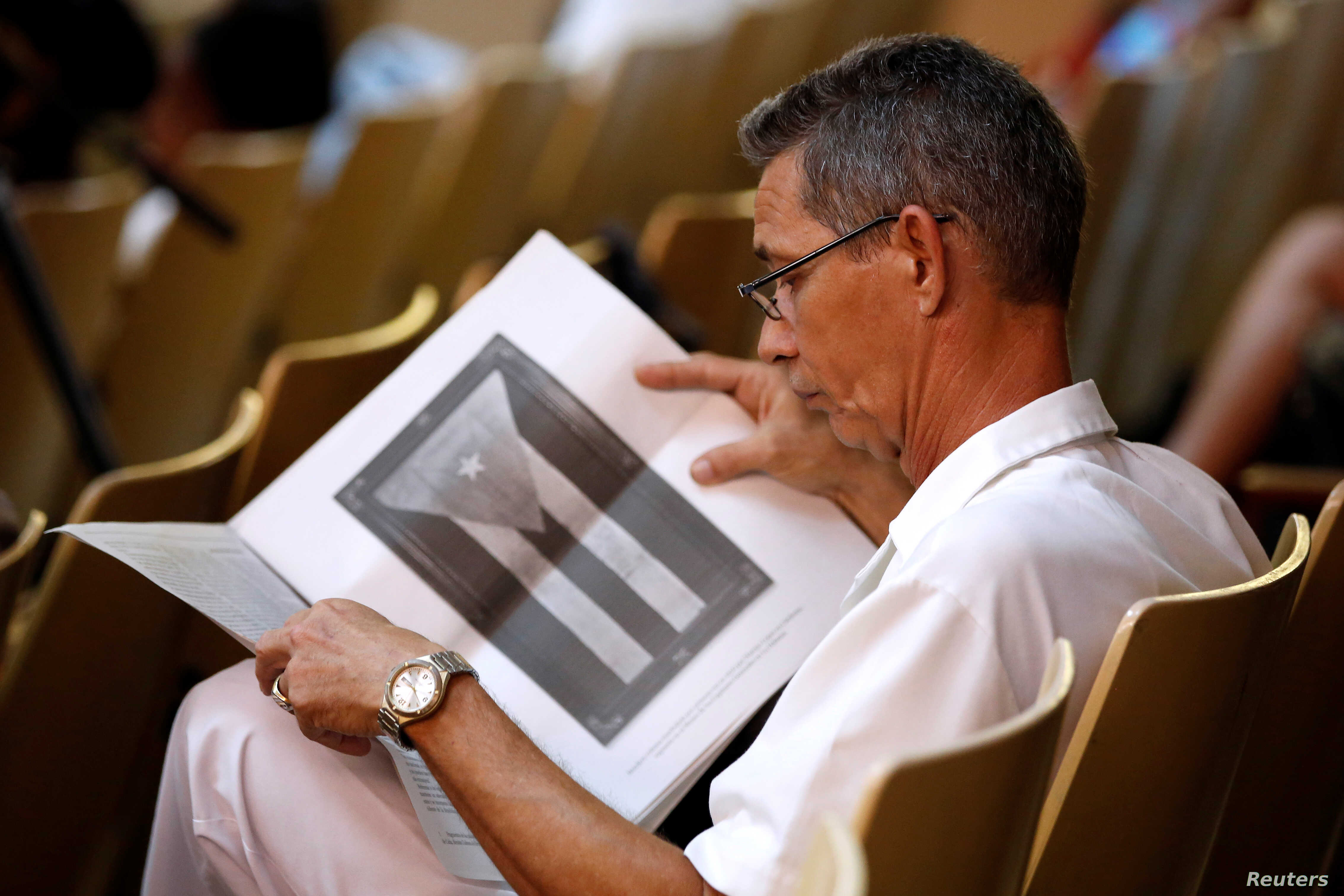 A Cuban reads the draft proposal of changes to the constitution during the beginning of a public political discussion to revamp a Cold War-era constitution at the Nguyen Van Troi Polyclinic in Havana, Aug. 13, 2018.
