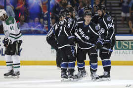 Tampa Bay Lightning's Ondrej Palat (18), of Czech Republic, is congratulated on his goal by teammates, including Tyler Johnson (9) and Nikita Kucherov (86), of Russia, as Dallas Stars' Gemel Smith reacts during the third period of an NHL hockey game,
