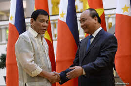 Philippines' President Rodrigo Duterte, left, greets Vietnamese Prime Minister Nguyen Xuan Phuc as they meet at Phuc's Cabinet Office in Hanoi on September 29, 2016.