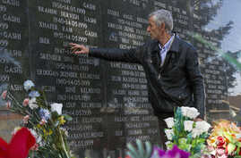 A survivor of the Cuska massacre points out the names of family members as he visits a cemetery in the village of Cuska, Kosovo, on Feb. 11, 2014.