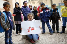 FILE - Syrian refugee Tesnim Faydo, 8, shows her drawing of a mother crying for her wounded daughter, as she is surrounded by her friends in Yayladagi refugee camp in Hatay province near the Turkish-Syrian border, Turkey, Dec. 16, 2015.
