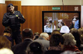 """A bailiff stands in a room as people watch a live broadcast of a court hearing on members of the female punk band """"Pussy Riot"""" in Moscow October 10, 2012. The court is hearing an appeal for three members of the band that was adjourned the week before"""