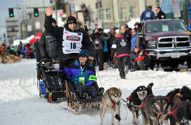 Defending Iditarod Trail Sled Dog Race champion Dallas Seavey waves to the crowd at the start line of the 1,000-mile race, in Anchorage, Alaska, March 5, 2016.