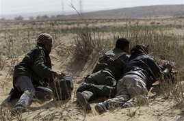 Libyan rebel take their position during a battle against pro-Moaamar Gadhafi fighters, in the town of Brega, east of Libya, March 2, 2011.