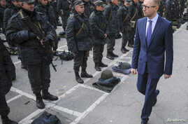 FILE - Ukrainian Prime Minister Arseniy Yatsenyuk (R) inspects servicemen and government defence forces outside Kyiv, Sept. 30, 2014.