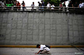 A woman kneels at the place where 17-year-old demonstrator Neomar Lander died during riots at a rally against Venezuelan President Nicolas Maduro's government in Caracas, Venezuela, June 8, 2017.