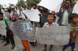 "FILE - A boy holds a banner reading ""Please stop grabbing our land"" at a rally by land evection victims in front of the National Assembly in Phnom Penh, Cambodia, Sept. 1, 2014."