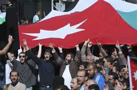 Jordanian supporters of the Islamic Action Front carry a national flag as they shout slogans during a protest in Amman, Jordan, February 25, 2011
