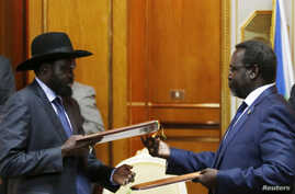 FILE -  South Sudan's President Salva Kiir (L) and the country's rebel leader, Riek Machar, exchange signed peace agreement documents in Addis Ababa May 9, 2014.