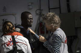 A migrant reacts as he is greeted by MSF workers aboard the MV Aquarius, as 193 people and two corpses are recovered, Jan. 13, 2017, from international waters in the Mediterranean Sea about 22 miles (35 Km) north of Sabrata, Libya.