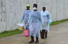 FILE - Health workers carry buckets of disinfectant at an Ebola treatment center in Monrovia, Liberia, Sept. 25, 2014.