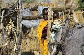 A woman carries her child at her shelter during a visit by Qatar's Minister of State for Foreign Affairs Ahmed Bin Abdullah Al-Mahmoud and UN/AU negotiator and Darfur chief mediator Djibril Bassole to Kalma internally displaced person (IDP) camp outs