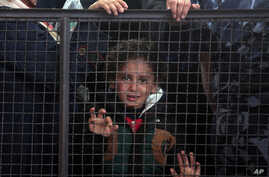 A Palestinian girl waits with her family for their turn to enter the Rafah border crossing with Egypt, in the southern Gaza Strip, May 11, 2016.