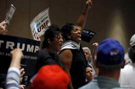 Protesters shout as they are escorted out of the building during U.S. Republican presidential candidate Donald Trump's campaign rally at the Tampa Convention Center in Tampa, Florida March 14, 2016.