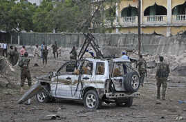 Soldiers stand near the wreckage of a car bomb attack that targeted a checkpoint in Mogadishu, Somalia, March 21, 2017.