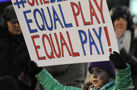 FILE - A girl holds up a sign for equal pay for the U.S. women soccer players, April 4, 2017, during the first half of an international friendly soccer match between the United States and Colombia, in East Hartford, Conn. A new study finds women are