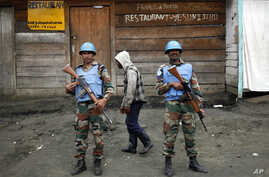 FILE - In this Friday Nov. 30, 2012 file photo, Two UN soldiers stand guard in Goma, Democratic Republic of Congo. Part of President Donald Trump's proposed deep budget cuts in foreign aid could be significant reductions in U.N. peacekeeping missions