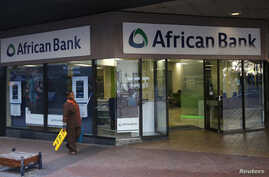 FILE - A cleaner walks past a branch of African Bank in Cape Town.