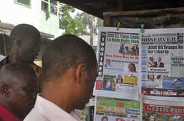 People read newspaper headlines commenting on U.S. President Barack Obama's announcement on sending troops to fight the Ebola virus in Monrovia, Liberia, Sept. 17, 2014.
