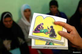 FILE - A counselor holds up cards used to educate women about female genital mutilation (FGM).