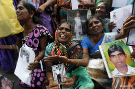 Tamil women cry as they hold up images of their disappeared family members during the war against Liberation Tigers of Tamil Eelam (LTTE) at a protest in Jaffna north of Colombo, Aug. 27, 2013.