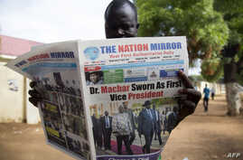 A resident reads a daily newspaper on April 27, 2016 reporting on the arrival and swearing-in of rebel leader Riek Machar in Juba, South Sudan, a day after his return.