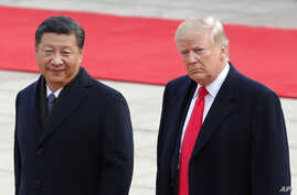 FILE - U.S. President Donald Trump, right, walks with Chinese President Xi Jinping during a welcome ceremony at the Great Hall of the people in Beijing, Nov. 9, 2017.