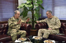 The U.S. chairman of the Joint Chiefs of Staff, Gen. Joseph Dunford, right, and Turkey's Chief of Staff Gen. Hulusi Akar talk during a meeting in Incirlik Airbase in Adana, Turkey, Feb. 17, 2017.