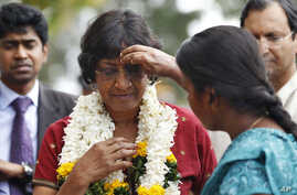FILE - A Sri Lankan ethnic Tamil girl applies vermillion on the forehead of U.N. High Commissioner for Human Rights Navi Pillay, in red, as she welcomes her at a vocational training center in Kilinochchi, Sri Lanka, Aug. 27, 2013.