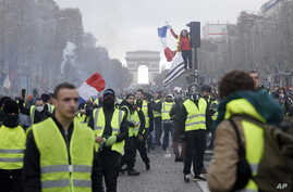 """FILE - In this Nov. 24, 2018, file photo, demonstrators, wearing """"yellow vests,"""" march on the Champs-Elysees in Paris, France, as they protest the rising of the fuel prices. (AP Photo/Kamil Zihnioglu, File)"""