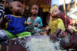 Internally displaced Somali children eat boiled rice outside their family's makeshift shelter at the Al-cadaala camp in Somalia's capital Mogadishu, March 6, 2017.