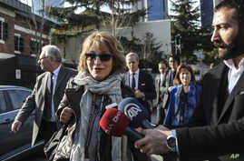 United Nations Special Rapporteur Agnes Callamard, surrounded by members of the media walks around the Saudi Consulate, background, in Istanbul, Turkey, Jan. 29, 2019.