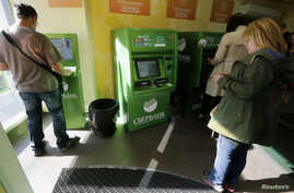 FILE - People use an ATM inside a branch of Sberbank in St. Petersburg, Russia, Sept. 16, 2014.