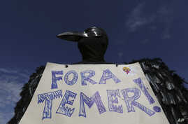 "A demonstrator dressed in a black feathered costume holds a sign telling Brazil's President Michel Temer to ""get out,"" during an anti-government protest in Brasilia, Brazil, May 24, 2017."