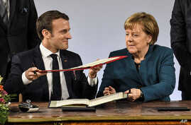 German chancellor Angela Merkel, right, and French President Emmanuel Macron, left, exchange documents during the signing of the new Germany-France friendship treaty at the historic Town Hall in Aachen, Germany, Jan. 22, 2019.