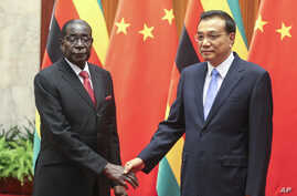Zimbabwean President Robert Mugabe, left, and Chinese Premier Li Keqiang pose for photographers prior to their meeting at the Great Hall of the People in Beijing, Aug. 26, 2014.
