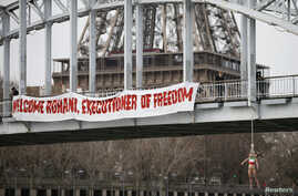 FILE - An activist hangs from a bridge to protest Iran's President Hassan Rouhani visit to Paris, January 28, 2016.