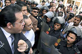 "Egyptian opposition politician Ayman Nour (L) argues with anti-riot policemen blocking the road in front of his party headquarters, as dozens of protesters chant ""freedom"" and call for amending the constitution to allow fairer presidential elections,"
