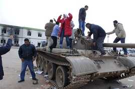 Residents stand on a tank inside a security forces compound in Benghazi, Libya, February 21, 2011