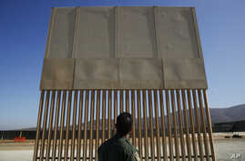 FILE - A U.S. Border Patrol agent looks at one of border wall prototypes in San Diego, June 28, 2018.