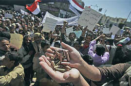 An anti-government protester displays bullet shells, claiming they were fired at demonstrators Tuesday night by Yemeni government supporters, killing at least one demonstrator, while demanding resignation of President Ali Abdullah Saleh, in Sanaa, Ye