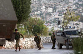 Israeli soldiers take positions during clashes with Palestinians as troops conduct a search for three missing Israeli teens in the West Bank village of Kabatyeh near Jenin, June 22, 2014.