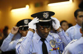 "An LAPD Cadet Commander adjusts his hat before the LAPD Cadet Program Graduation of the cadet ""Class of 7-2014""."