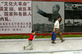 Visitors walk past a portrait of the late Chinese leader Mao Zedong at the Cultural Revolution Museum in Shantou in China's southern Guangdong province May 15, 2006.