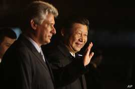 China's President Xi Jinping, center, waves to the press accompanied by Cuba's Vice President Miguel Diaz-Canel, left, at his arrival at the Jose Marti International Airport in Havana, Cuba, July 21, 2014.