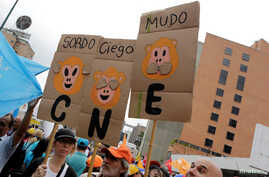 """Opposition supporters hold placards during a rally to demand a referendum to remove President Nicolas Maduro in Caracas, Venezuela, May 14, 2016. From left, the placards read """"Deaf,"""" """"Blind"""" and """"Dumb."""" """"CNE"""" on the placards refers to the National El"""